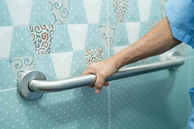 Azjatycka starsza kobieta używa uchwytu bezpieczeństwa w toalecie w szpitalu