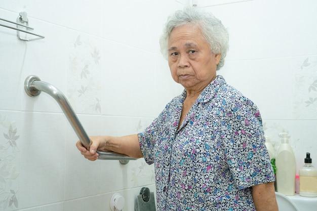 Azjatycka starsza kobieta używa uchwytu bezpieczeństwa w toalecie