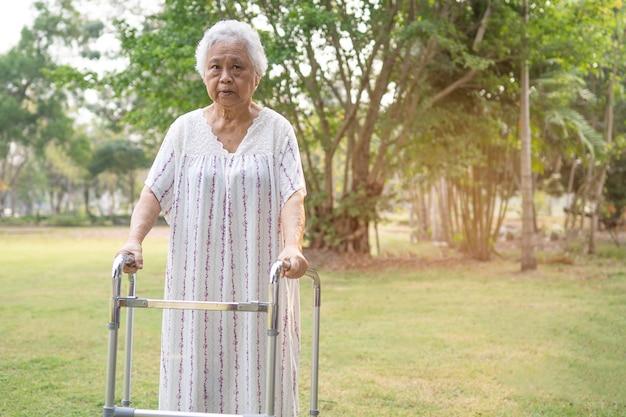 Azjatycka starsza kobieta używa walker w parku.