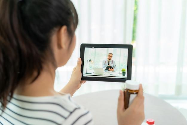 Azjatycka starsza kobieta używa wideokonferencję, robi konsultację online z lekarzem konsultuje się na temat choroby i leków za pośrednictwem połączenia wideo. telezdrowie, telemedycyna i szpital online.