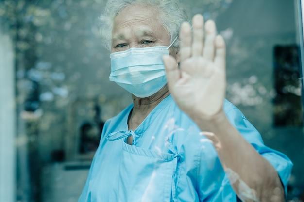 Azjatycka starsza kobieta z maską patrzącą przez okno na kwarantannę podczas koronawirusa