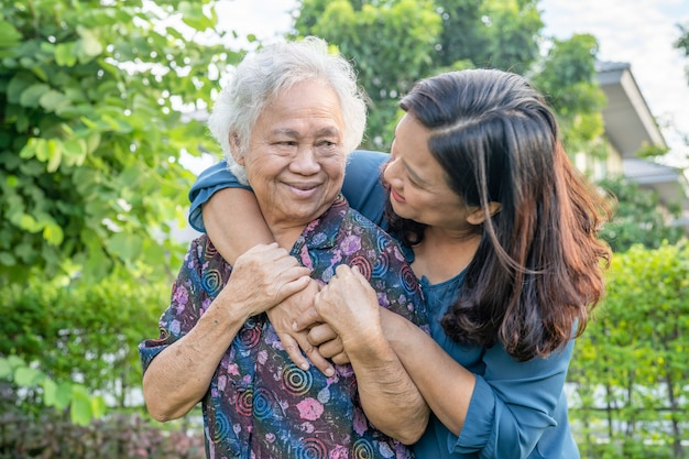 Azjatycka starsza kobieta z opiekunem chodzenie z szczęśliwym w parku przyrody.