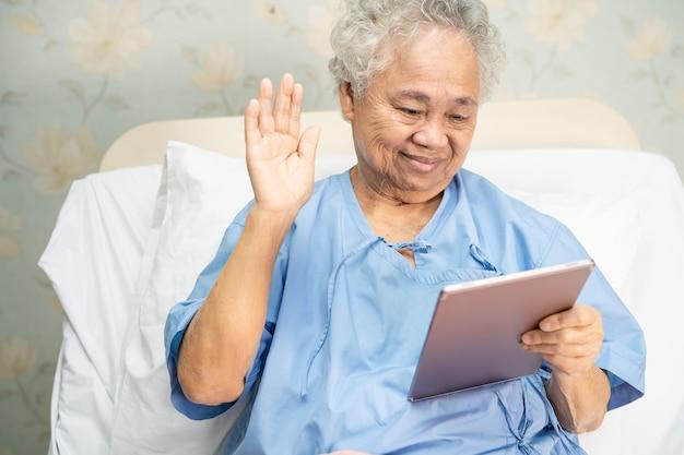Azjatycka starsza kobieta za pomocą cyfrowego tabletu do połączenia wideo.