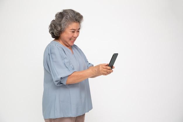 Azjatycka starsza kobieta za pomocą smartfona na na białym tle nad białą ścianą.