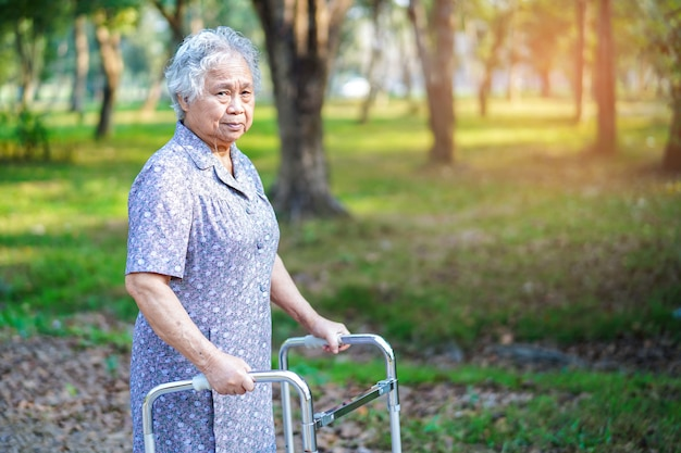 Azjatycka starsza lub starsza stara dama używa piechura z silnym zdrowie podczas gdy chodzący przy parkiem.