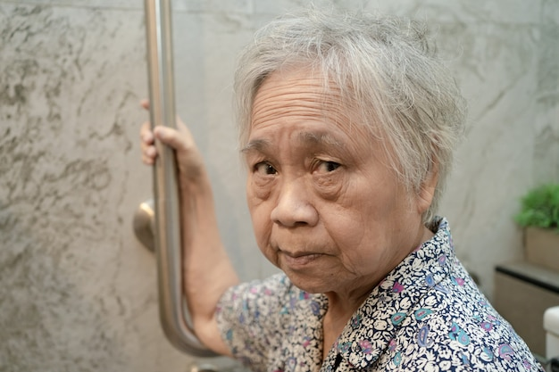 Azjatycka starsza lub starsza starsza kobieta pacjent korzysta z toalety łazienka uchwyt bezpieczeństwa na oddziale szpitala pielęgniarskiego, zdrowa, silna koncepcja medyczna.