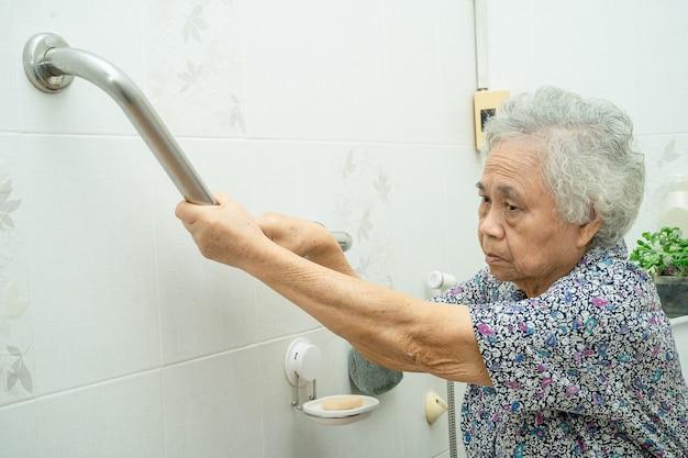 Azjatycka starsza lub starsza starsza kobieta pacjent używa uchwytu bezpieczeństwa z pomocą asystenta wsparcia w oddziale szpitala pielęgniarskiego zdrowa silna koncepcja medyczna