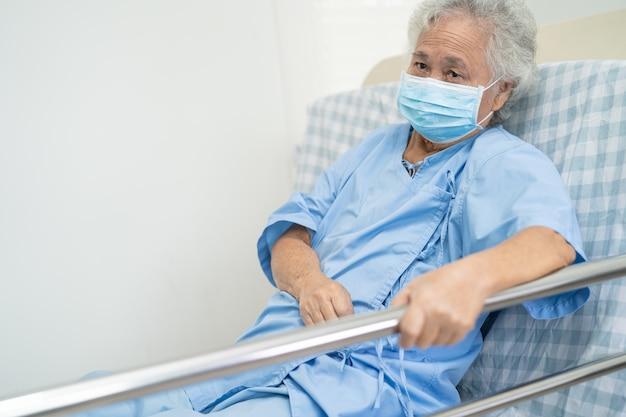 Azjatycka starsza lub starsza starsza kobieta pacjentka kładzie się, obsługuje łóżko poręczowe z nadzieją w szpitalu