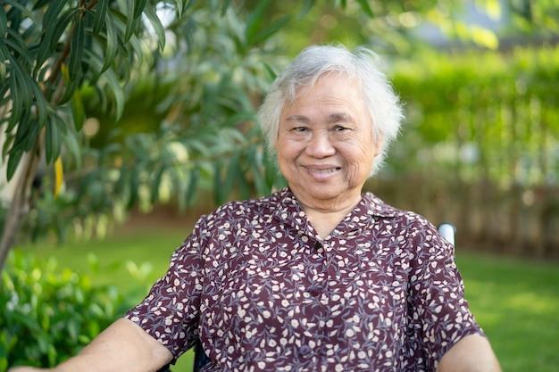 Azjatycka starsza lub starsza starsza kobieta uśmiech pacjenta na wózku inwalidzkim w parku, zdrowa, silna koncepcja medyczna