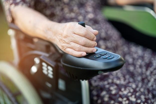 Azjatycka starsza lub starsza starsza pani pacjentka na elektrycznym wózku inwalidzkim z pilotem na oddziale szpitala pielęgniarskiego, zdrowa, silna koncepcja medyczna
