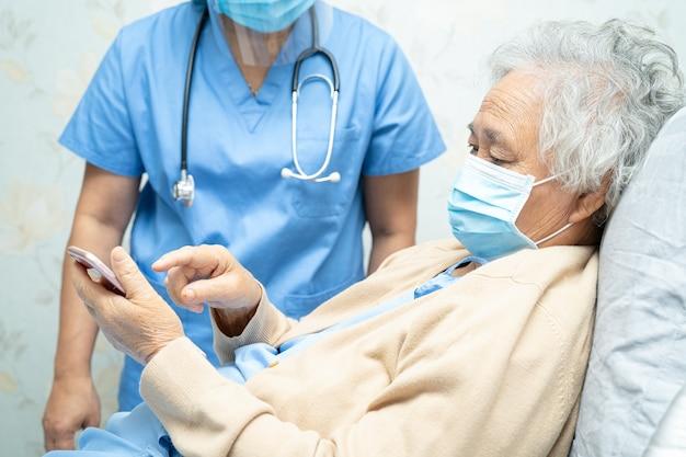 Azjatycka starsza pacjentka nosząca maskę na twarz i trzymająca telefon komórkowy w szpitalu w celu ochrony koronawirusa covid19