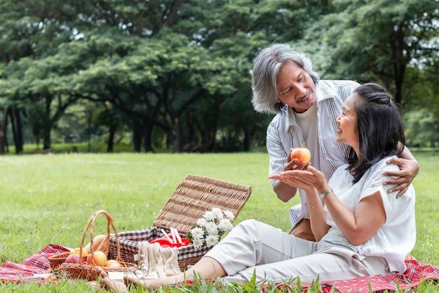 Azjatycka starsza para relaksuje i piknik przy parkiem. żona daje jabłka mój mąż.