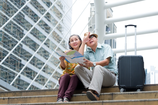 Azjatycka starsza para siedzi trzymając mapę, aby wyszukać miejsca docelowe na ulicach dużego miasta