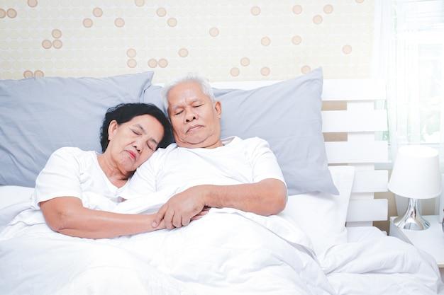 Azjatycka starsza para śpi w łóżku w sypialni.