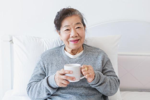 Azjatycka starsza stara kobieta pije kawę lub herbaty na łóżku