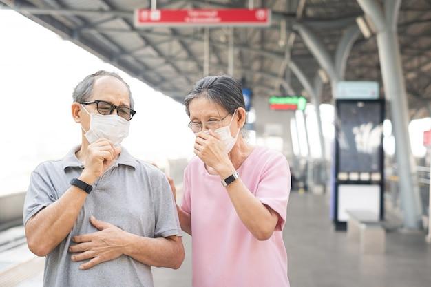 Azjatycka starsza starsza para jest ubranym maskę dla zapobiegać zakażeniu covid-19 lub koronawirusem na dworcu kolejowym.