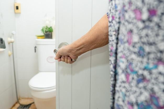 Azjatycka starsza starsza starsza kobieta pacjentka otwarta toaleta łazienka ręcznie w oddziale szpitala pielęgniarskiego, zdrowa, silna koncepcja medyczna.