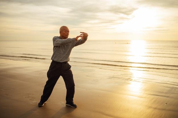 Azjatycka starsza stary człowiek praktyki tai chi i joga poza na plażowym wschodzie słońca