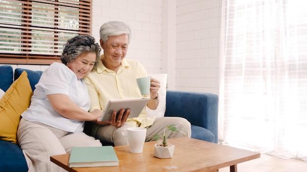 Azjatycka starszej osoby para używa pastylkę i pijący kawę w żywym pokoju w domu, para cieszy się miłość moment podczas gdy kłamający na kanapie gdy relaksujący w domu.