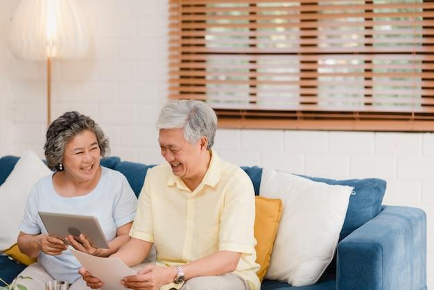 Azjatycka starszej osoby para używa pastylkę ogląda tv w żywym pokoju w domu, para cieszy się miłość moment podczas gdy kłamający na kanapie gdy relaksujący w domu.