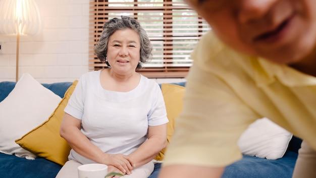 Azjatycka starszej osoby para używa smartphone wideokonferencja z wnukiem podczas gdy kłamający na kanapie w żywym pokoju w domu.