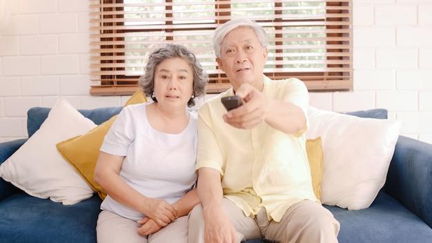 Azjatycka starszej osoby pary dopatrywania telewizja w żywym pokoju w domu, słodka para cieszy się miłość moment podczas gdy kłamający na kanapie gdy relaksujący w domu.