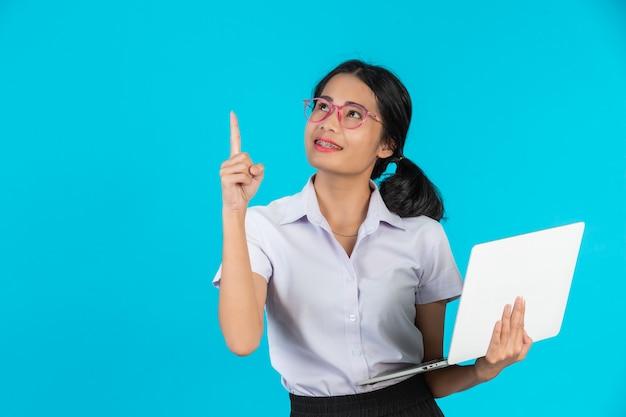 Azjatycka studencka dziewczyna trzyma jej notatnika na błękicie.