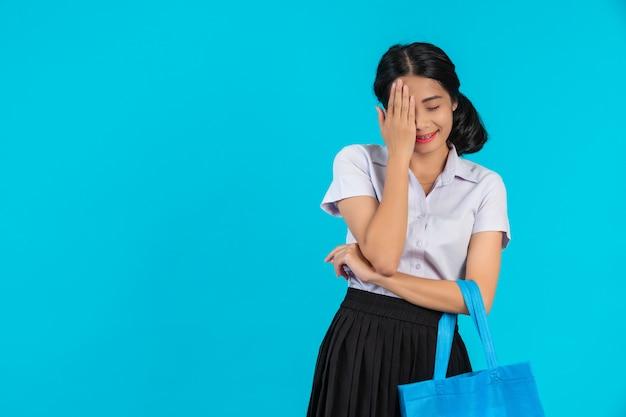 Azjatycka studentka, która obraca sukienną torbę i pokazuje różne gesty na niebiesko.