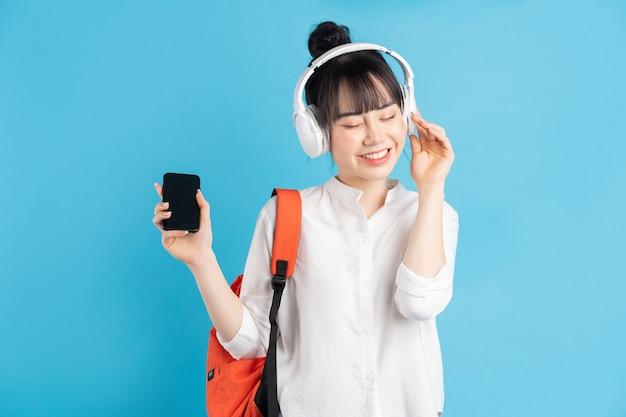 Azjatycka studentka nosi plecak za plecami, trzyma smartfon, szyję w bezprzewodowych słuchawkach, trzyma papierowy kubek