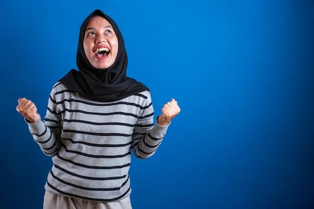 Azjatycka studentka w chuście na głowie świętująca sukces z uniesionymi rękami i zaciśniętymi pięściami