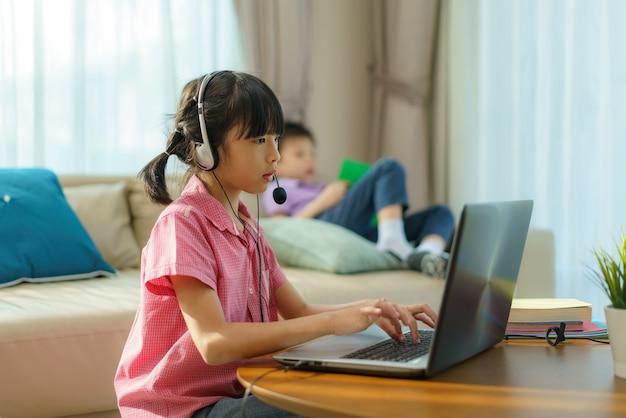 Azjatycka studentka wideokonferencji e-learning z nauczycielem i kolegami z klasy na komputerze oraz z książką rodzeństwa na sofie w salonie w domu
