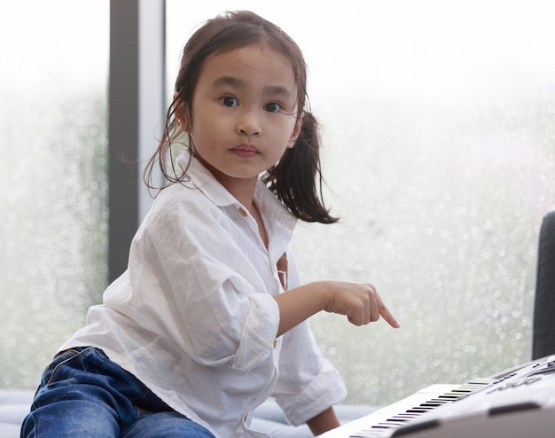 Azjatycka szczęśliwa dziewczyna gra na pianinie w sali ćwiczeń muzycznych, atmosfera na zewnątrz pada. kropelki wody na szkle. koncepcja urocza edukacja naukowa.