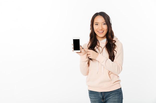 Azjatycka szczęśliwa kobieta pokazuje pokazu telefon komórkowy.