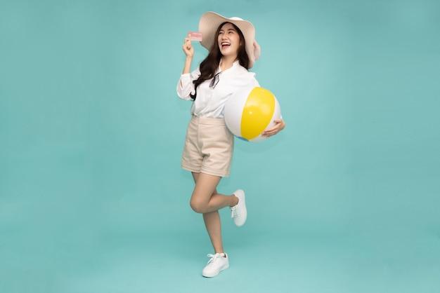 Azjatycka szczęśliwa kobieta stoi i trzyma kartę kredytową z piłką