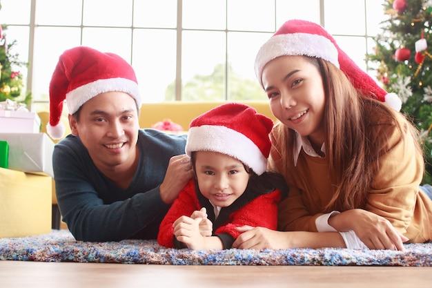 Azjatycka szczęśliwa młoda rodzina z dziećmi bawiącymi się z okazji bożego narodzenia. czas świąt. mój tata, mama i córka w mikołajowych czapkach leżą na kanapie w domu. koncepcja śliczna przytulna szczęście.