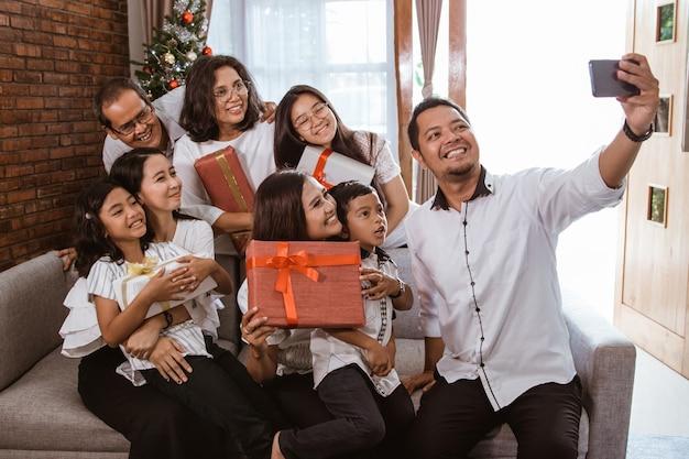 Azjatycka szczęśliwa rodzina razem świętuje boże narodzenie w domu