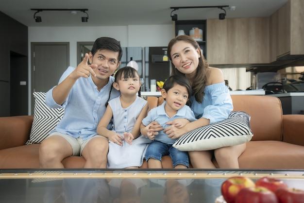 Azjatycka szczęśliwa rodzina siedzi i ogląda telewizję w salonie w domu i spędza razem czas na zajęciach w dzień wakacji