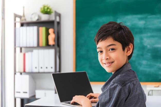 Azjatycka szczęśliwa szkolna chłopiec używa laptop na czerni desce