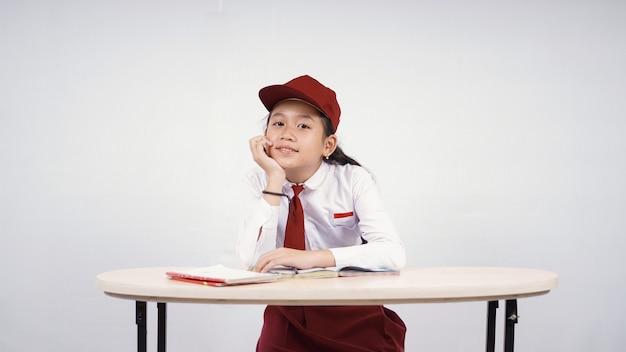Azjatycka szkoła podstawowa dziewczyna studiująca cieszy się na białym tle