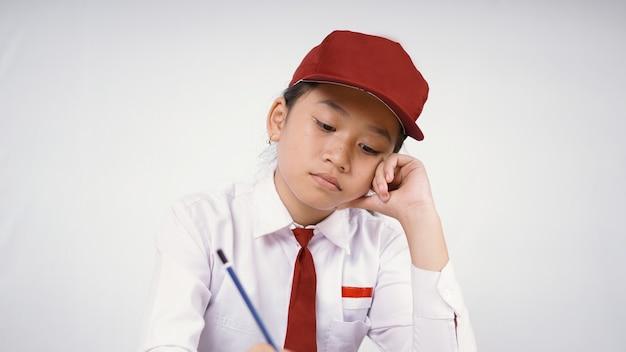 Azjatycka szkoła podstawowa dziewczyna uczy się do zmęczenia na białym tle