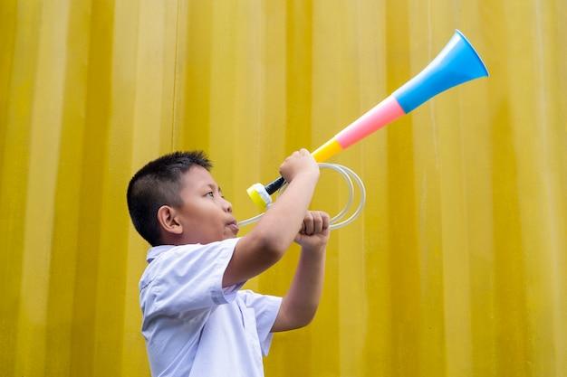 Azjatycka szkolna chłopiec dmucha kolorowego róg w żółtym tle.