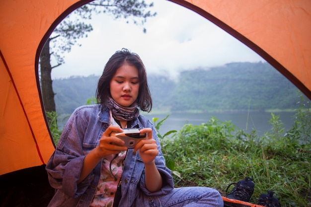 Azjatycka turystka cieszy się pięknem natury z aparatem, czując się szczęśliwa