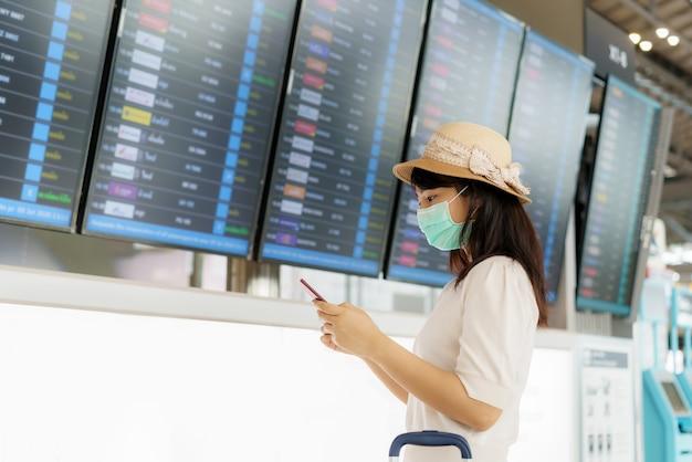 Azjatycka turystka kobieta ubrana w maskę, sprawdzanie lotu z tablicy przylotów i odlotów