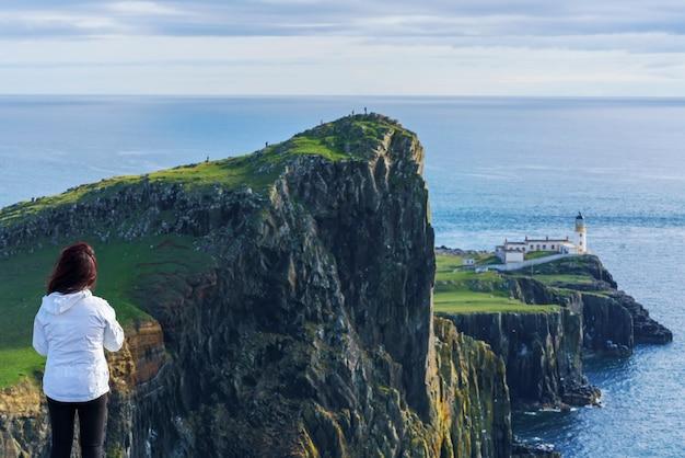 Azjatycka turystka patrząc na słynną latarnię morską neist point położoną na zachodnim wybrzeżu skye w obszarze znanym jako durinish , isle of skye , szkocja