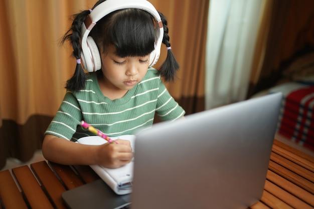 Azjatycka uczennica, dziewczynka w słuchawkach, uczy się online w domu, oglądając lekcje internetowe lub słuchając nauczyciela przez połączenie wideo