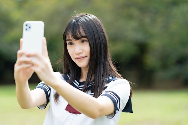 Azjatycka uczennica liceum dotykając ekranu smartfona
