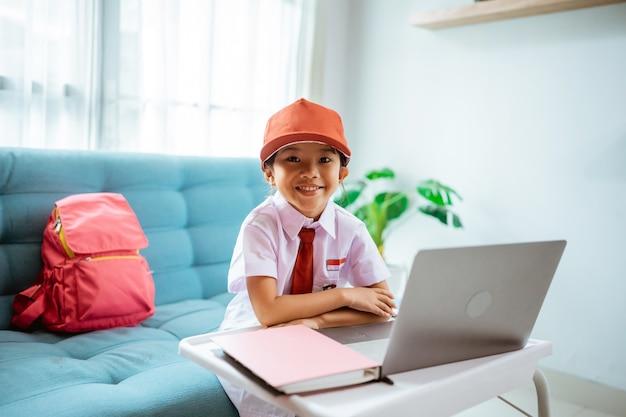 Azjatycka uczennica szkoły podstawowej patrząca w kamerę i uśmiechająca się w indonezyjskim mundurku szkolnym podczas lekcji online w domu