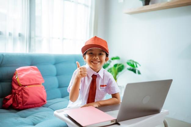 Azjatycka uczennica szkoły podstawowej pokazująca kciuk w górę podczas korzystania z laptopa podczas sesji online w mundurku szkolnym