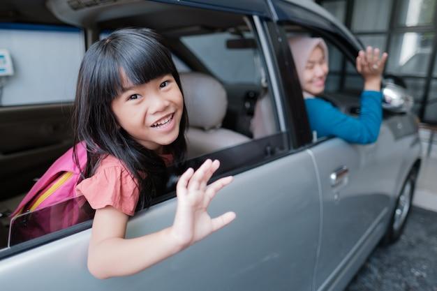 Azjatycka uczennica szkoły podstawowej siedząca w samochodzie i machająca na pożegnanie rano idąc do szkoły