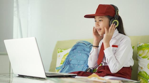 Azjatycka uczennica szkoły podstawowej studiująca online słuchanie muzyki przez słuchawki w domu
